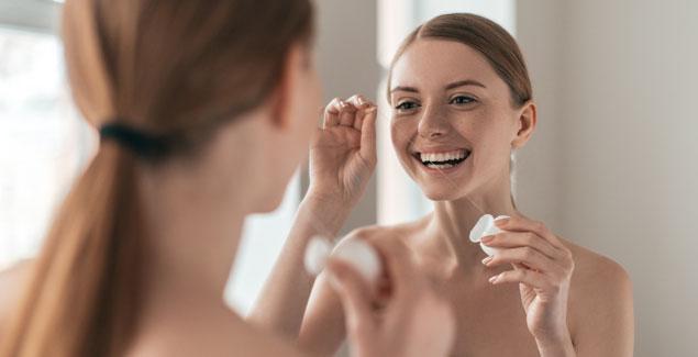 Woman flosses teeth in the mirror